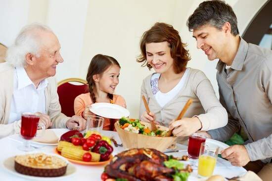 Portrait of happy family sitting at festive table while having T