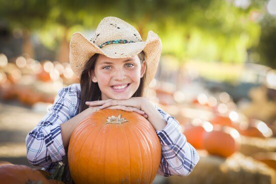 Portrait of Preteen Girl Wearing Cowboy Hat Playing at the Pumpk