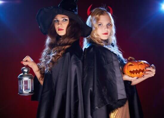 Two witches with lantern and pumpkin looking at camera in the da